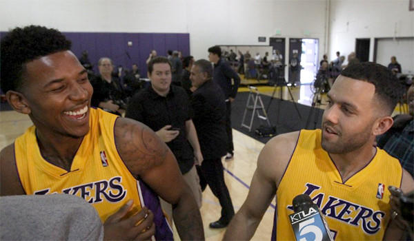 Lakers guards Nick Young, left, and Jordan Farmar, right, share a light moment during media day at the Lakers' training facility Saturday.