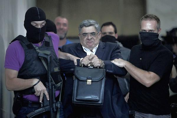 Nikos Michaloliakos, leader of Greece's far-right Golden Dawn party, is escorted by masked police officers Saturday to the prosecutor from police headquarters in Athens.