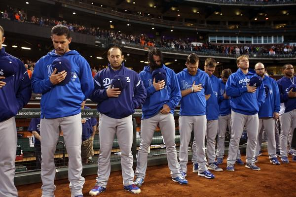 Los Angeles Dodgers players bow their heads during a moment of silence for the death of 24-year-old Jonathan Denver before a game at AT&T Park in San Francisco, California, on Sept. 26, 2013.