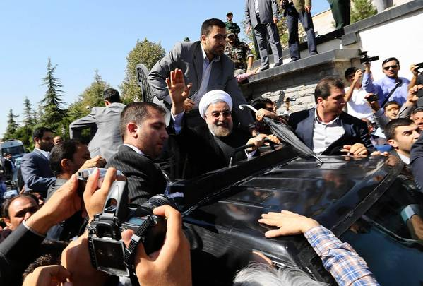 Iranian President Hassan Rouhani greets supporters who welcomed him upon his arrival at Tehran's Mehrabad International Airport. A group of dissenters also appeared, throwing shoes and eggs.