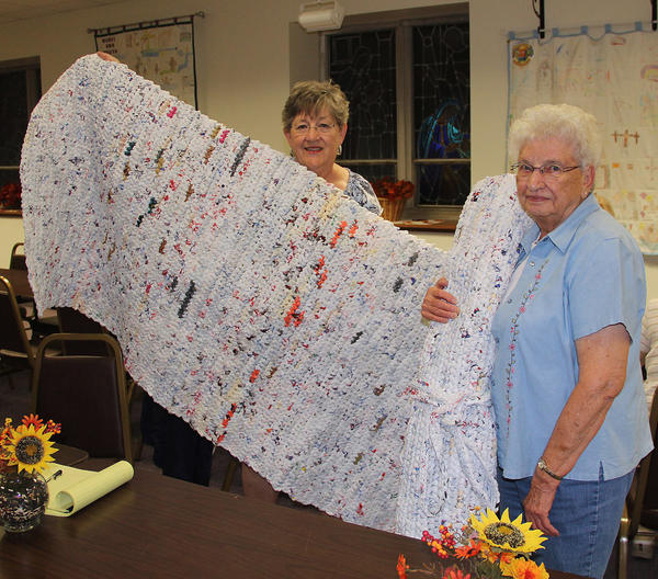 From left, Rayma Scepaniak and Vi Schnaidt display a finished product, a sleeping mat made from recycled plastic bags.