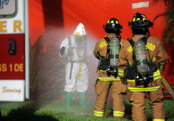A Hollywood Fire Rescue hazmat firefighter is hosed down after entering a home tented for termites which burglars attempted to rob, Sunday, Sept. 29, 2013, on the 1200 block of Harrison St. Nobody was found in the home..Joe Cavaretta, SunSentinel (c)2013....