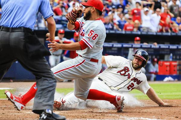 Evan Gattis of the Atlanta Braves scores on a passed ball before Cesar Jimenez of the Philadelphia Phillies can make the tag at Turner Field on Sunday.