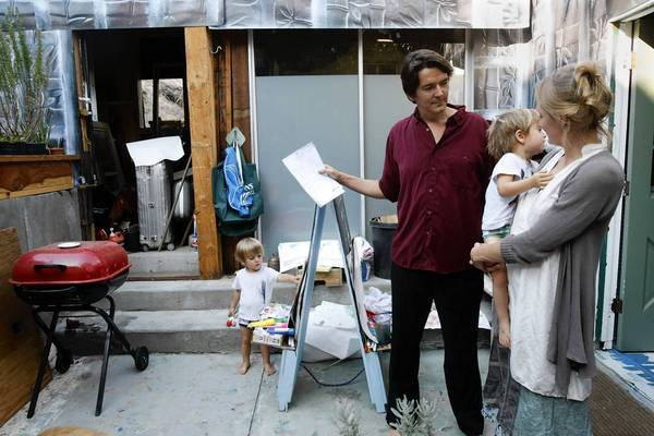 John Sullivan and his wife, Carrie Dennis, stand on the porch of their Hollywood home with their twins, Finneas, left, and Atticus. The fixer-upper duplex seemed perfect for the two artists -- until all the hassles with building rules and regulations began.