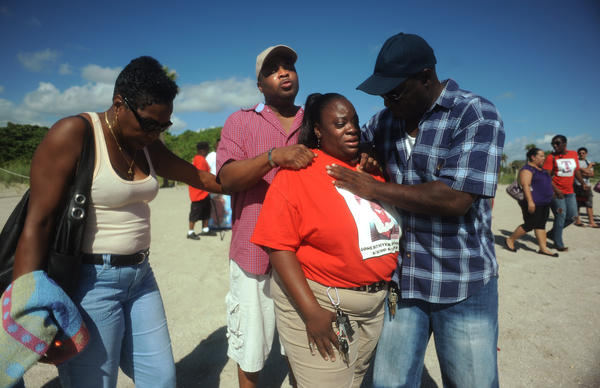 Chrisie Snell and James Clark, center, parents of Jamal Clark, are comforted by relatives Sylvia and Joel Cunningham on Sunday.