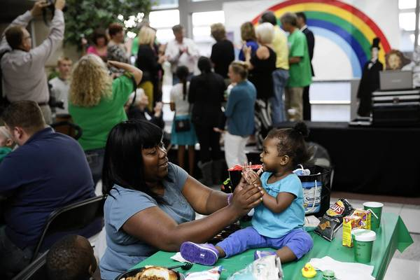 Lolita Lee-Johnson claps with her 1-year-old daughter Jada Johnson during a neonatal intensive care unit-related reunion of families and medical care workers Sunday at the University of Chicago Medicine Comer Children's Hospital. The family of Weber grill creator George Stephen announced a $10 million donation to the neonatal ICU during the event.