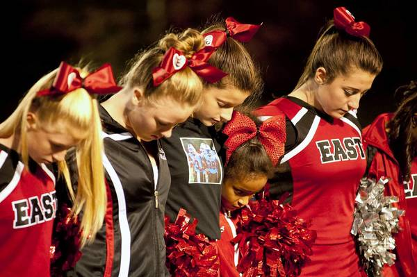 Pocono Mountain East cheerleaders observe a moment of silence before the Cardinals' first home game since the car accident that left two classmates, Steven Dienno and Justin Bullock, severely injured