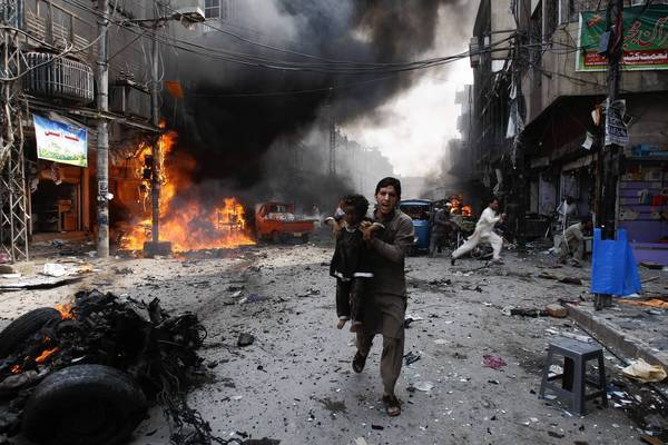 A man carries a child from the blast site at a bazaar in Peshawar, Pakistan, after a massive car bomb exploded.