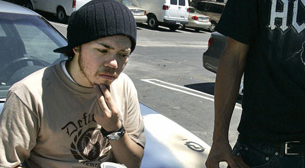 Birmingham High School dropout Elias Fuentes spends an idle moment in the parking lot of a Van Nuys restaurant.