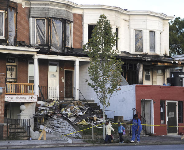 Pedestrians walk by the scene of a fire aftermath on the 4600 block of York Road near at the intersection with Cold Spring Lane.