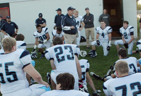 Petoskey High School varsity football coach Kerry VanOrman (middle) addresses his team prior to the Northmen taking to the field Friday against Cheboygan at Western Avenue Field in Cheboygan. The Northmen fell to the Chiefs, 9-6, to fall to 2-3 on the season.