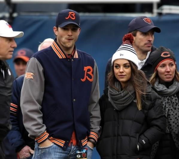 Actors Ashton Kutcher (left) and Mila Kunis (right) watch pre-game warm ups before Chicago Bears play Green Bay Packers at Soldier Field Dec. 16, 2012.