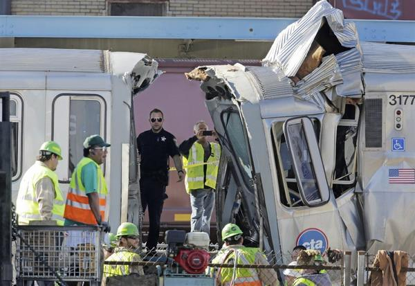 Authorities inspect the wreckage of two Chicago Transit Authority trains that crashed Monday, Sept. 30, 2013, in Forest Park, Ill. The crash happened when a westbound train stopped at the CTA Blue Line Harlem station and was struck by an eastbound train on the same track.