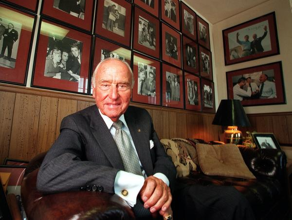 A.C. Lyles in his office at Paramount Studios in July 1998. Behind him are pictures of himself and movie stars and presidents he was friends with.