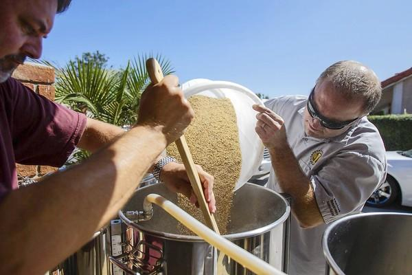 Jon Welfringer, left, and Brian Cockle pour milled grain into a kettle in preparation for mashing an American Pale Ale. Welfringer brews his own beer out of his garage in Huntington Beach.