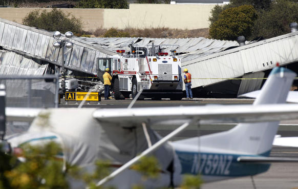 Santa Monica firefighters monitor the collapsed aircraft hangar where a private jet crashed and burned Sunday evening at Santa Monica Airport. Investigators will have to lift the hangar's metal roof off the burned aircraft to determine how many bodies are inside.