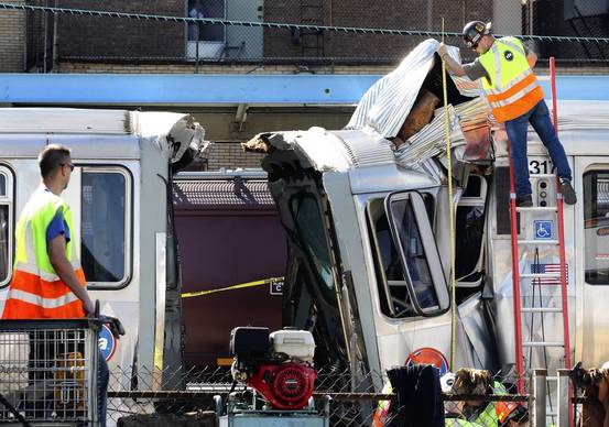 CTA workers measure the height of the crumpled metal after two Blue Line CTA trains collided at the Harlem stop in Forest Park.