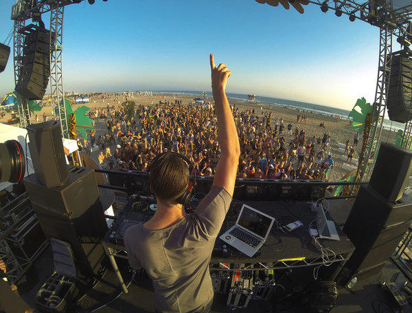 DJ Mak J of Los Angeles gets the crowd going at an all-day rave at Huntington Beach on Sept. 14. More than 100 people were arrested on mostly alcohol- and drug-related charges at a Bay Area rave over the weekend.