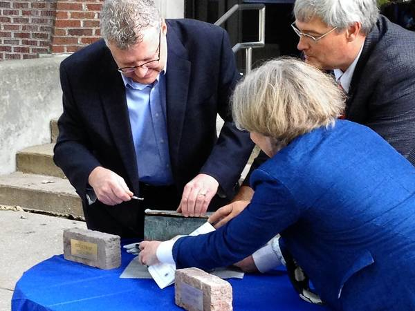 "Paul Coultrap, assisted by his sister Martha and Superintendent Kent Mutchler, pries open a time capsule at a recent dedication ceremony of the central office as the ""Coultrap Educational Services Center."""