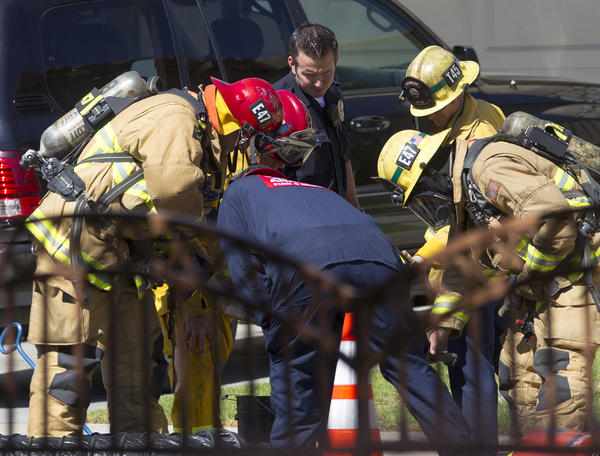 Rescue personnel from Anaheim Search and Rescue, Huntington Beach fire and police departments survey the scene of an underground electrical vault fire on Humboldt Island in Huntington Harbour.