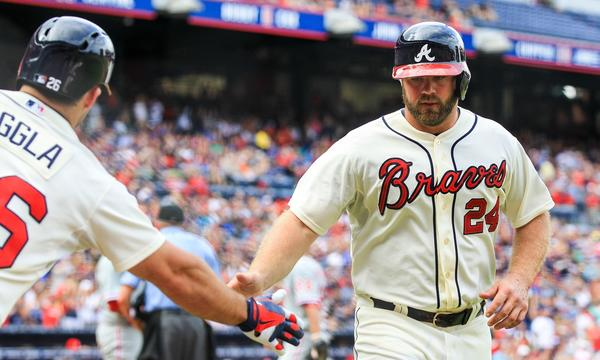 Atlanta's Evan Gattis, right, is congratulated by teammate Dan Uggla after scoring a run against the Philadelphia Phillies on Sunday. Some players on the Braves are upset the Dodgers are favored by some to win their National League division series playoff.
