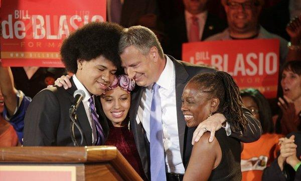 In this Sept. 10, 2013 file photo, New York Democratic mayoral candidate Bill de Blasio embraces his son Dante, left, daughter Chiara, second from left, and wife Chirlane McCray, right, after polls closed in the city's primary election in New York.