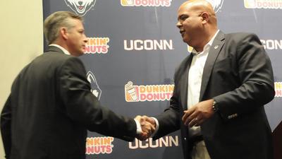 AD Warde Manuel de UConn, derecha, le da la mano a su nuevo entrenador de ftbol, T.J. Weist, durante la conferencia de prensa del lunes.