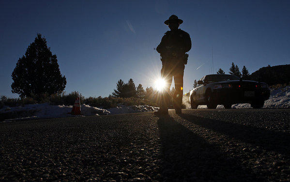 A California Highway Patrol officer mans a roadblock on California 38 on Feb. 13, near where Christopher Dorner fired on two San Bernardino County sheriff's deputies, killing one. The second deputy returned to work Monday.