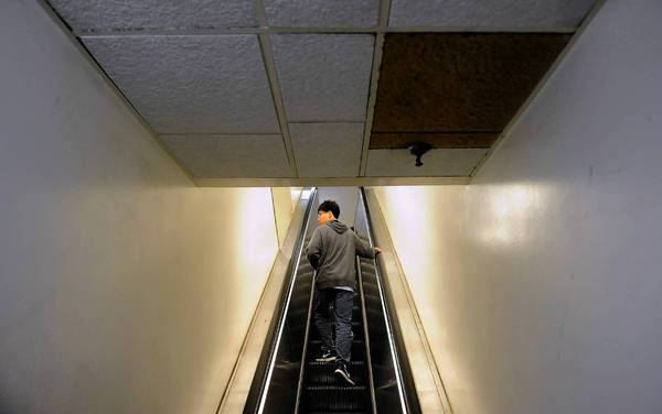 The Cal State Board of Trustees' proposed 2014-15 budget plan seeks an additional $250 million from the state, including $75 million to increase student enrollment and an initial $15 million to help finance up to $800 million in bonds for maintenance needs. Above, a student rides up an escalator past an oil-stained ceiling panel at Cal State Fullerton. The oil comes from the 50-year-old escalator's motor.