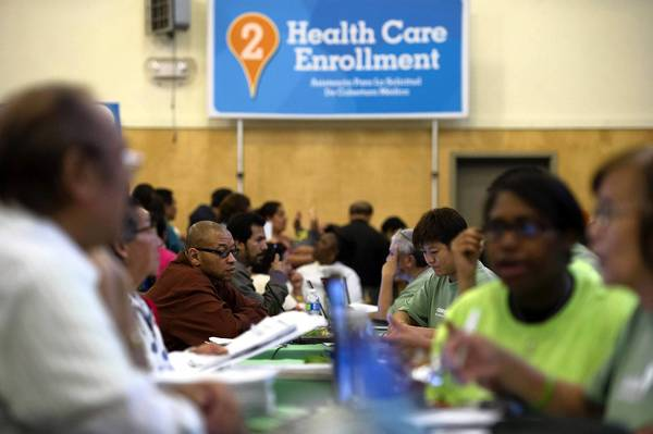 Volunteers explain the new healthcare law at an event in Oakland. The Obama administration is encouraging uninsured Americans to shop for plans at new online exchanges starting Tuesday. Some Republican opponents are urging people not to sign up.