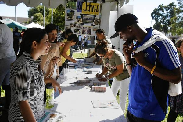 Lizzeth Henao Rosales, left, speaks with Carlos Spivey, right, at the South L.A. Power Festival. Spivey, 30, went to the festival to find out more about Obamacare.