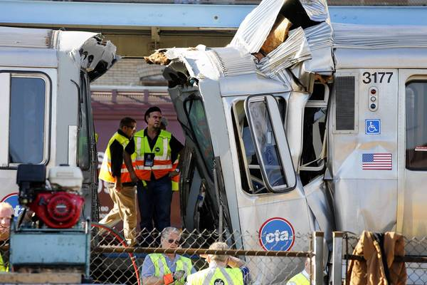Officials examine the damage to an out-of-service CTA rail car that ran head-on into a stopped train at a Blue Line station in Forest Park Monday morning.
