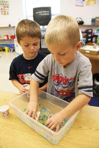 Logan LaBrie looks on as Kaiden Howard plays with water beads Thursday morning in the Doland preschool room.