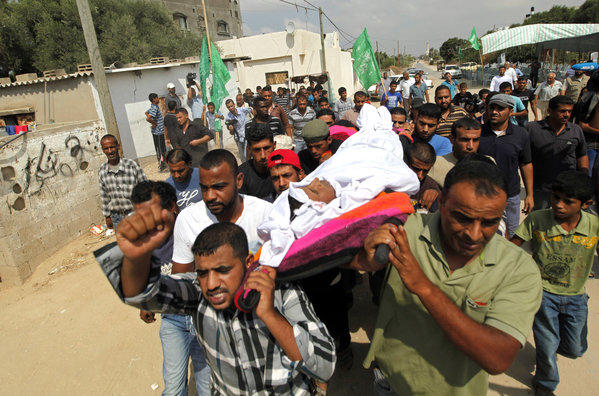 Palestinians carry the body of Hiwashel Abu Hiwashel, 36, who was killed Monday by Israeli soldiers, during his funeral Tuesday in central Gaza Strip.