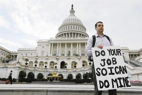 A furloughed federal employee holds sign on the steps to the U.S. Capitol after the U.S. Government shut down last night, on Capitol Hill in Washington.