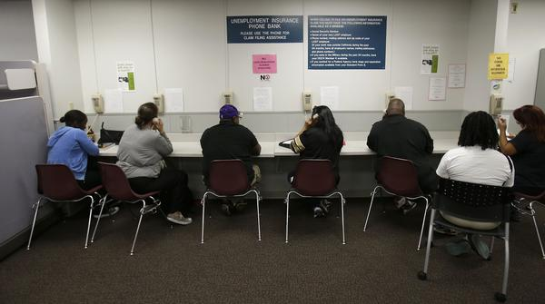 California's Employment Development Department says all backlogged unemployment benefits claims have been processed. Here, visitors use the unemployment insurance phone bank at the EDD office in Sacramento.