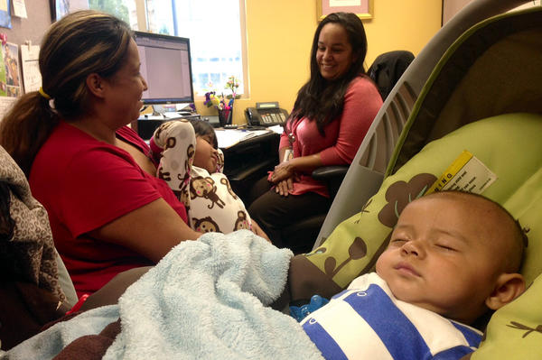 Annette Diaz holds her daughter, Kayla Valenzuela, 2, while her son Johnie Valenzuela, 5 months, sleeps, in the Health Benefits Resource Center at St. Francis Medical Center in Lynwood, one of many locations providing information about the start of Obamacare.
