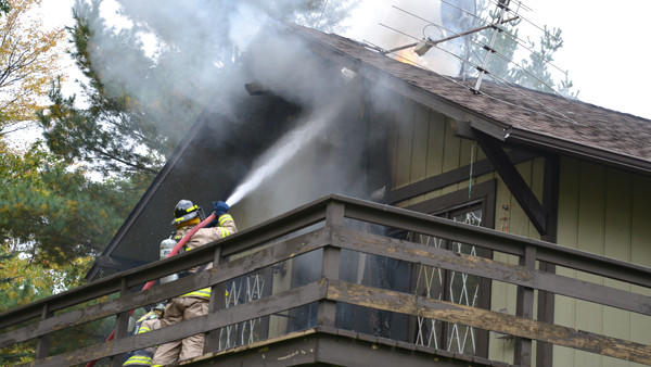 Firefighters douse flames visible on the roof of the home at 8765 Summit Dr. Tuesday. HT - Chris Engle