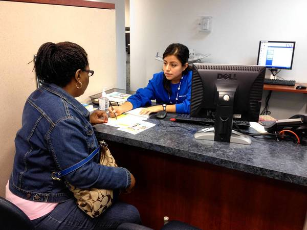 Gilda Garcia, an in-person counselor for VNA Health Care in Aurora, talks to Aretha Robertson, 50, of Yorkville, about her health insurance options under the Affordable Care Act on Tuesday morning.