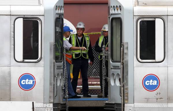 National Transportation Safety Board investigators and CTA officials try to determine the cause of an out of service CTA train ramming into a train stopped at a Blue Line station in Forest Park on Monday, sending more than 30 people to hospitals