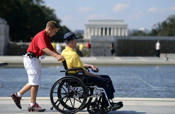 Zach Twedt pushes Robert Olson, a Korean War veteran, on a tour of the World War II Memorial in Washington.