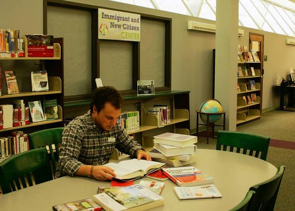 Jason Pinshower, adult services librarian, reviews some of the resources available to members at the Immigrant/New Citizen Center at the Indian Trails Library District.
