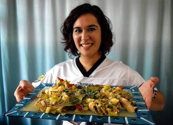 Beth Norman holds a dish of bacalao with green sauce