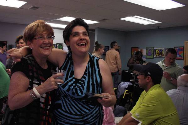 Diane Turner, left, and her daughter Rebecca Turner, right, pose for a picture during an art exhibition on Sept. 27 put on by The Arts of Life, a nonprofit that serves adults with and without disabilities. Rebecca, who has a previous developmental delay, has been attending the organization's studio in Glenview to express her creativity.