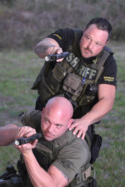 "Broward sheriff's deputies Gerald Wengert, at bottom, and Geoff Brown have been named in an excessive-use-of-force lawsuit. They were featured in the now-defunct series ""Unleashed: K-9 Broward County."""