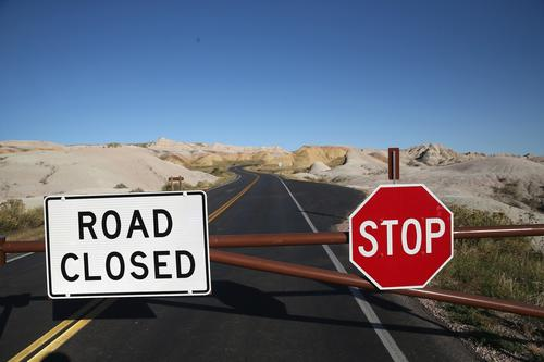 A barricade prevents visitors from entering the interior of the Badlands National Park near Wall, S.D. All national parks were closed after Congress failed to pass a temporary funding bill.