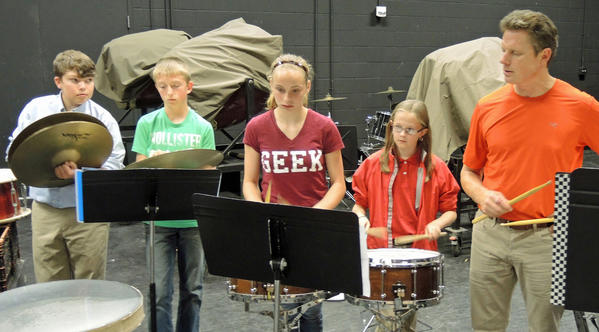 Band director Barry Bennett (right) taps out rhythms with seventh grade percussionists (from left) Peter Molosky, Kyle Porath, Paige Smith and Madi Law.. .