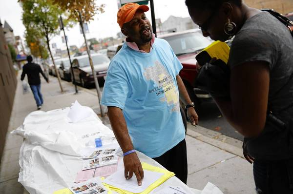 "Larry Dixon hands out literature on the Affordable Care Act on Tuesday at the Lawndale Christian Health Center on Chicago's West Side. Many of the people approaching him had questions, he said. ""No one explained this stuff to these people,"" Dixon said."