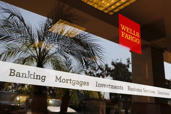 New York Atty. Gen. Eric Schneiderman plans to file a lawsuit against Wells Fargo, the largest mortgage lender and servicer. Above, palm trees are reflected in the window of a bank branch in Hermosa Beach.