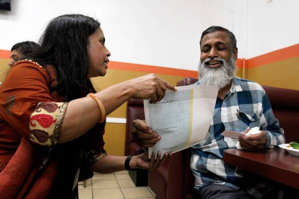 Nina Sharmin, left, informs Taher Majumder about Covered California at Deshi Restaurant in L.A.'s Little Bangladesh neighborhood.